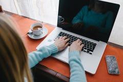 Женщина печатая на клавиатуре компьтер-книжки с кофейной чашкой на таблице Стоковые Изображения