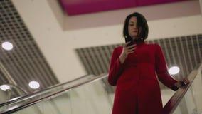 Женщина печатая на приборе smartphone пока двигающ дальше эскалатор видеоматериал