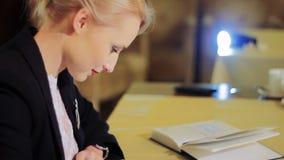 Женщина печатая на сенсорной панели сидя на таблице видеоматериал
