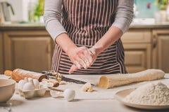 Женщина печет пироги Кондитер делает десерты Делать плюшки Тесто на таблице тесто замешивает Стоковая Фотография RF