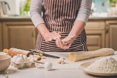 Женщина печет пироги Кондитер делает десерты Делать плюшки Тесто на таблице тесто замешивает Стоковое фото RF