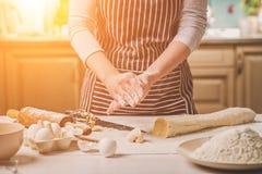 Женщина печет пироги Кондитер делает десерты Делать плюшки Тесто на таблице тесто замешивает Стоковая Фотография