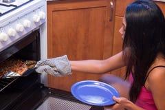 Женщина печет пиццу стоковые изображения