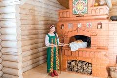 Женщина печет хлеб в русской плите стоковые фото