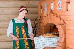 Женщина печет хлеб в русской плите стоковая фотография