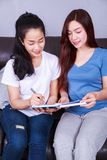 Женщина 2 пишет книгу на софе в живущей комнате дома Стоковое Изображение RF