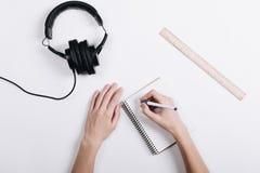 Женщина пишет ручку в тетради на белой таблице, следующей голове лож Стоковые Изображения RF