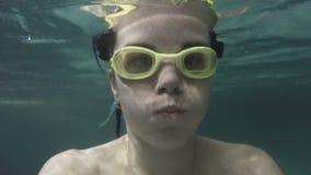 Женщина плавает под водой Портрет ` s женщины конца-вверх внутри гуглит видеоматериал