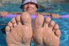 Женщина плавая в бассейн, держа крутой стоковые изображения rf
