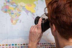 женщина планирует путешествия за рубежом, принимает фото карту стоковое фото rf