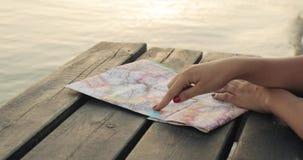 Женщина планируя маршрут отключения на карте на пристани на заходе солнца, крупном плане моря рук видеоматериал