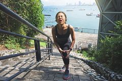 Женщина плача для тягостного ушиба колена пока работающ Стоковое Изображение RF