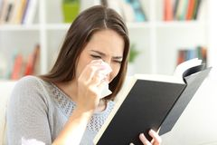 Женщина плача пока читает бумажную книгу дома стоковая фотография