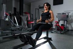 Женщина плюс размер в спортзале делая тренировки с приборами тренировки, стоковые изображения
