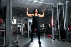 Женщина плюс размер в спортзале делая тренировки с приборами тренировки, стоковое фото