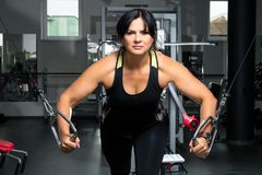 Женщина плюс размер в спортзале делая тренировки с приборами тренировки, стоковое изображение rf