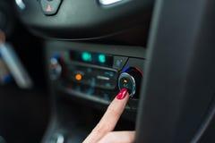 Женщина поворачивая дальше условие воздуха автомобиля стоковое фото rf