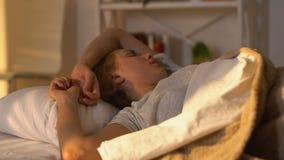 Женщина поворачивая под одеяло, едва ли просыпающся в утре, расписание спать сток-видео