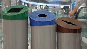 Женщина повторно использует бумагу в мусорный бак со знаком бумаги, пластмассы и стеклянных Ненужные сортировать и повторно испол акции видеоматериалы