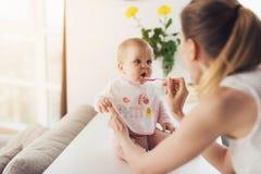 Женщина подает младенец с ложкой Ребенок сидит на таблице в кухне и ест с удовольствием Стоковые Фото