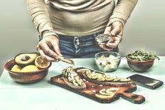 Женщина подготавливает сандвичи с авокадоом и arugula дома здоровая заедк Стоковые Фотографии RF