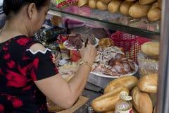 Женщина подготавливает сэндвич в улице Хошимина, Вьетнама стоковые изображения rf