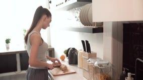 Женщина подготавливая завтрак, режа хлеб на борту в кухне видеоматериал