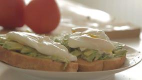 Женщина подготавливая здоровый завтрак с авокадоом на зажаренных в духовке хлебе, яйцах и томате сток-видео