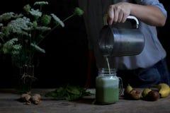 Женщина подготавливая зеленый и белый smoothie с смоквами, банан, waln стоковое фото rf