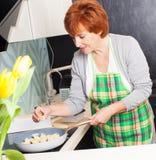 Женщина подготавливая макаронные изделия дома стоковое изображение