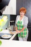 Женщина подготавливая макаронные изделия дома стоковые фото
