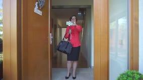 Женщина подготавливая снять на двери телефона дома акции видеоматериалы
