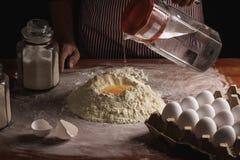 Женщина подготавливая тесто с ее руками стоковая фотография rf