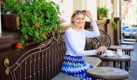 Женщина подмигивая стороне имеет террасу кафа питья outdoors Чай питья девушки с молоком как великородная традиция Кружка хорошег стоковая фотография