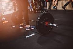 Женщина поднимает бар в спортзале Стоковые Изображения RF
