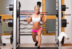 Женщина поднимает гантели в спортивном центре для того чтобы развить мышцы стоковая фотография rf