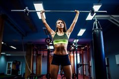 Женщина поднимая crossfit веса в спортзале Штанга deadlift женщины фитнеса Стоковые Изображения
