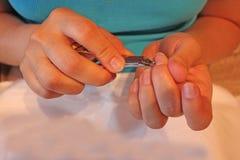 Женщина подрезая ее руки заботы пальца ногтей стоковые фото