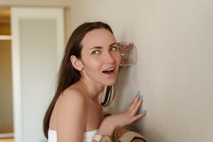 Женщина подслушивая через стену комнаты через стеклянную чашку, любопытства, шпионажа, удивленной стороны, ярких эмоций стоковое фото