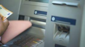 Женщина подсчитывая евро разделенные от ATM, кладя получает внутри портмоне наличными, удобство сток-видео