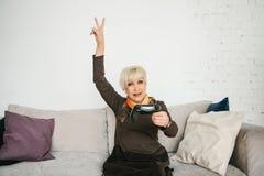 Женщина пожилых людей играет видеоигру и жесты которую она выиграла Пожилая персона и современная технология Стоковое фото RF