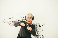 Женщина пожилых людей играет видеоигру и разделена в пикселы Схематическое фото с значить визуальных эффектов Стоковые Фото