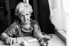 Женщина пожилых людей измеряет артериальное давление Стоковая Фотография RF