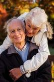 Женщина пожилых людей обнимает ее супруга сидя на стенде смотря камеру Стоковое Изображение RF