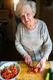Женщина пожилых людей прерывает овощи для салата овощ Стоковые Изображения RF