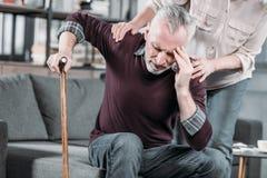 Женщина позаботить о старший супруг с сильной головной болью стоковая фотография