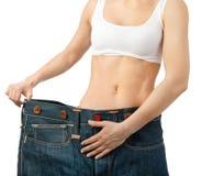 Женщина показывает ее потере веса путем носить старые джинсыы, изолированные дальше стоковые фотографии rf
