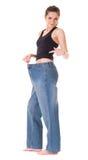 Женщина показывает ей старые огромные джинсыы, потерю wieght стоковые изображения