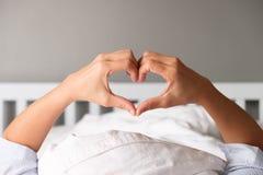 Женщина показывает жест вручную в форме сердца стоковое фото rf