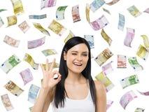 Женщина показывает одобренный знак Примечания евро падают вниз над изолированной предпосылкой Стоковое фото RF